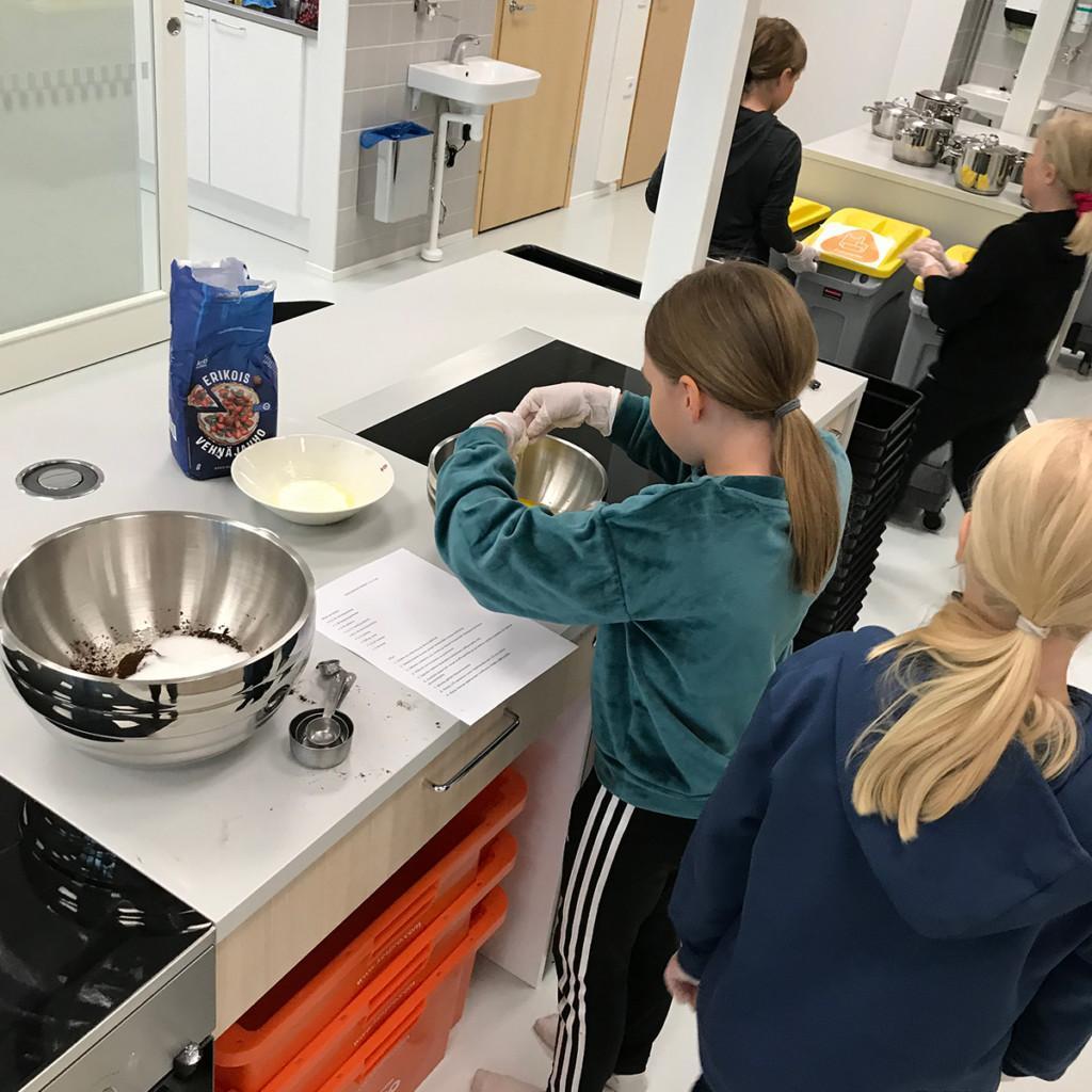 Lapset leipovat kakkua kokkauskurssilla.
